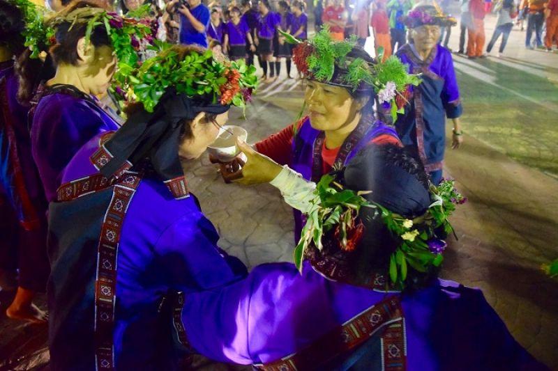 每年農曆9月15日舉辦的小林夜祭,是部落一大盛事。族人齊聚公廨前,牽戲(唱歌跳舞)祝禱太祖降臨。圖為神職人員「山豬婆」在為太祖服務,向族人敬酒。(圖片/Mata Taiwan 提供)