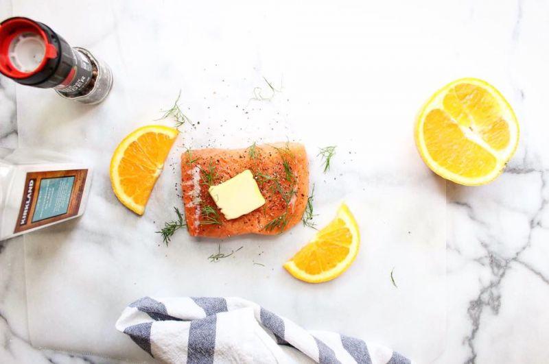 烤箱預熱425℉(300℃)。裁兩張烘培紙,長和寬約為鮭魚排的3倍。將一片鮭魚放在烘培紙中央,均勻撒上適量鹽和黑胡椒,再放上1又1/2小匙的無鹽奶油、1大匙的蒔蘿、2片柳橙。