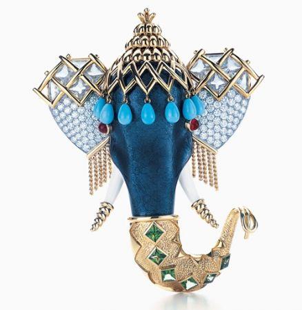 Tiffany由設計師Jean Schlumberger設計的印度神像胸針,以鉑金與18K金襯底,灰色琺瑯作象鼻,白色瑪瑙作象牙,飾以鋪鑲鑽石、綠松石、粉紅剛玉以及綠色的沙弗來石等寶石,華麗堆疊出慶典中的印度神像。