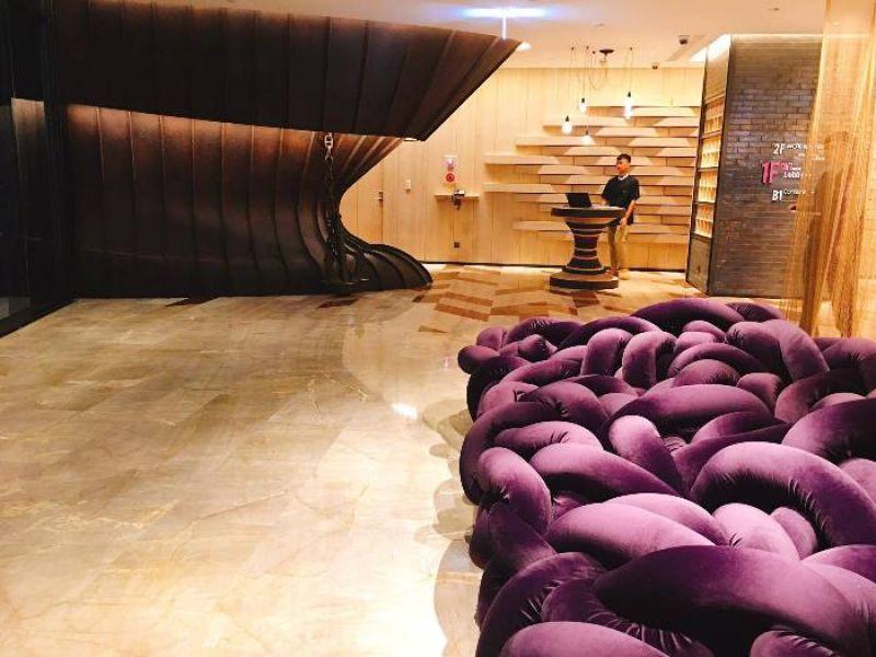 高雄中央公園英迪格酒店Lobby右側,紫色法蘭絨的大型裝置藝術沙發,交織的粗繩,象徵港口繫船纜繩,金色的鐵網隱喻漁網意象