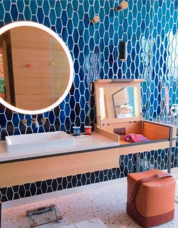 和房間同樣寬敞的盥洗更衣室,牆面馬賽克磚拼出漁網般的網眼狀;化妝鏡椅靈感來自旅人的舶來品皮革皮箱;造型化妝鏡上的軸線則是表現海港常會出現的垂吊輪軸