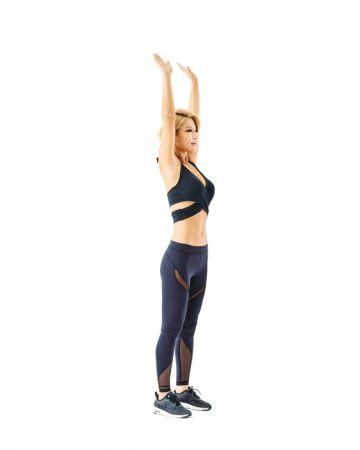 《站姿抬膝》伸展瘦肚肚1 身體站直,雙手往上高舉擺出歡呼的姿勢,同時要努力縮小腹。