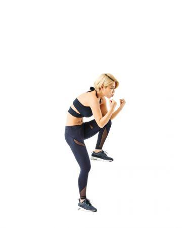 2 左腳膝蓋往胸口方向抬起,同時上半身往下收。腹部施力,讓膝蓋可以自然夾在雙手手肘之間, 左右各做100次。