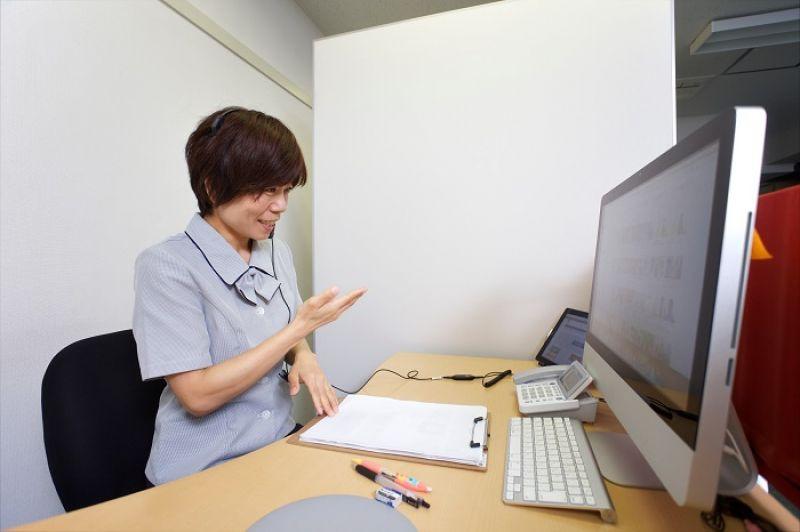 在東京 ShuR 的辦公室裡,手語翻譯者正透過視訊影片,回答失聰朋友的問題