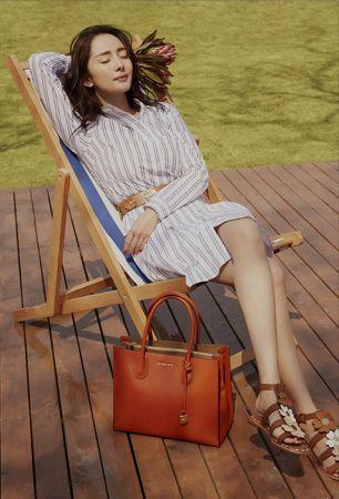 Look 2藍白條紋襯衫洋裝,利用腰帶做出纖細腰身的視覺,搭上橘色系的花朵涼鞋和Mercer包,充滿慵懶的度假風格