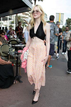 Elle Fanning坎城影展第二天,Elle Fanning換上短版上衣和淺橘印花長裙展現傲人腹肌,看似休閒的裝扮利用間頭黑色高跟鞋增加俐落感
