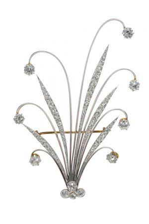 Tiffany 羽飾 (1890 - 1900)黃金、鉑金與鑽石9.7 x 6.8 x 1.3 cm由簇擁在中央的鑽石與向外四散的長條形葉片組成,背面配有胸針夾,底部配備螺絲裝置用於固定羽毛,這種髮飾稱為羽飾,靈感來自土耳其帝國風格頭飾中帶有羽毛的珠寶飾品。羽飾於1890年至1981年的Blue Book中首度出現,廣受19至20世紀女性的喜愛,隨著這種風潮的流行,羽飾在世紀之交成為大熱門飾品,同時髮夾、冠飾和髮圈等新款髮飾也日益普及。到了1908年,羽飾逐漸從Blue Book消失,取而代之的是髮帶與髮夾。隨著時尚風潮的變遷,原本用於固定頭髮的齒梳逐漸消失,轉變為胸針款式。