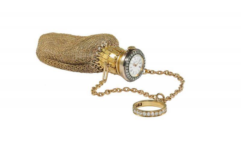 Tiffany附時計的戒環手袋 (1897 - 1903)黃金、鑽石、黃銅、水晶與琺瑯11.4 x 2.5 cm這款網狀設計手袋,頸部可伸縮,嵌有一枚時計。手袋與鑲鑽指環之間由兩根鏈條相連。時計錶盤飾有黑色羅馬字母和路易式指針,四周鑲嵌鑽石,並刻有Tiffany品牌標誌,字體與公司創始人Charles Lewis Tiffany的簽名相同。1897年至1903年的Blue Book出現了帶鑽石錶圈時計的黃金網眼手拿包。Bertha M. White Harrison夫人是這款網眼手袋的原物主,她是商人William Welsh Harrison之妻,她的丈夫與兄弟共同擁有富蘭克林煉糖廠。他們居住的灰塔莊園位於費城的格倫賽德,占地面積138公頃,建於1893年,共設有40個房間。這座莊園曾一度成為美國最大的私人宅邸。現在,此莊園已併入阿卡迪亞大學校園。