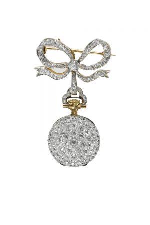 Tiffany胸針懷錶 Lapel Watch (1895 - 1917)黃金、鉑金、鑽石、水晶與琺瑯5.3 x 3 x 1.2 cm佚名瑞士機芯這款鋪鑲鑽石的女士懷錶,採用白色琺瑯錶盤與阿拉伯數字,搭配路易十五風格指針,並搭配一枚鑲嵌鑽石的胸針。胸針上的蝴蝶結造型展現Tiffany花環風格的典型特點:輕盈、靈動、柔美。懷錶被認為是日常珠寶,女性經常將它們別在左肩下方。這些懷錶是19世紀深受喜愛的高科技產品,如同當今最新款的iPhone一般備受世人追捧。Tiffany銷售多款女士時計,1895年的Blue Book就以3頁篇幅來展示不同的時計。Tiffany直至1917年才停止銷售胸針懷錶。