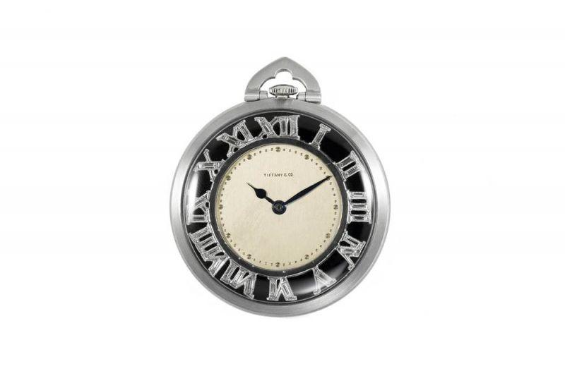 "Tiffany懷錶 (1925 - 1929)鉑金、鑽石、玻璃與琺瑯5.0 x 4.1 x 1.8 cm這是一款男士懷錶,採用銀質錶盤搭配羅斯高夫黑桃指針 (Roskopf spade-style hands),而黑色琺瑯外圈刻度環帶有鑲嵌矩形切割鑽石的羅馬數字。1920年代,隨著腕錶逐漸受到大眾認可,懷錶的受歡迎程度開始下降。懷錶的主要用途仍是搭配正式的晚宴服裝。Tiffany在1920年代初期的廣告中同時推廣了品牌的懷錶及腕錶,到了1929年,Tiffany開始單獨推廣腕錶。這一時期打造的懷錶展現出當時的時尚風格與優雅設計。Tiffany使用 ""超薄""、 ""纖薄"" 或 ""纖細""等等詞句來形容這些懷錶。"
