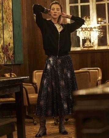 白色針織上衣、亮片裝飾褶裙、太空人圖案連帽外套、亮粉裝飾短靴、鑽飾項鍊,造型手鐲多只,all by Chanel。