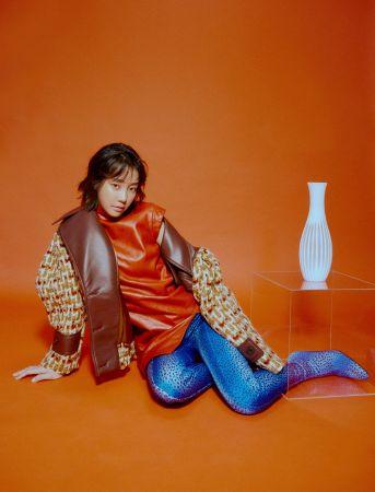 紅色皮革洋裝,毛呢拼接寬肩外套,both by Miu Miu;圖案印花彈性連褲襪靴,Balenciaga。