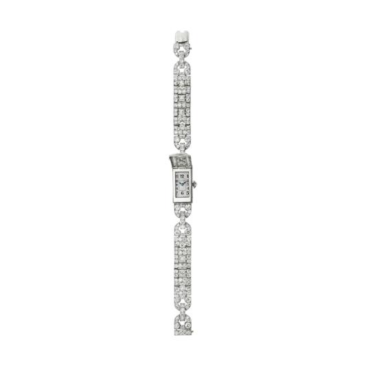 卡地亞古董珍藏系列「Savonnette」腕錶 裝飾藝術時期(1918 – 1939) 卡地亞巴黎,1932年 鉑金、鑽石,參考價格約NT$ 10,600,000矩形白金錶殼,四邊鑲嵌突起長方形切割鑽石,閃耀生輝的鑽石伴隨著印有CARTIER字樣的白色錶面,襯托出黑色阿拉伯數字、藍鋼指針、鏡面拋光錶圈、由玫瑰切割鑽石圍繞的錶冠、半球形錶耳,可伸縮錶鏈由兩個鏤空橢圓形部分構成,鋪鑲圓形切割鑽石。