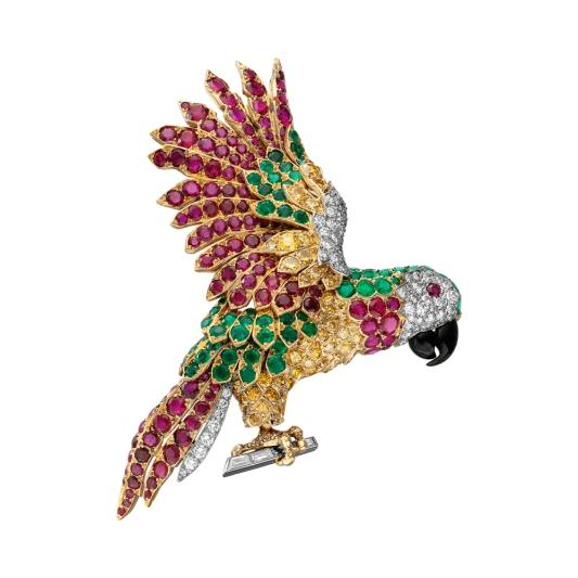 卡地亞古董珍藏系列鸚鵡造型夾式胸針 新女性風格時期(1939 – 1970) 卡地亞巴黎,1962年 黃金和玫瑰金、鉑、祖母綠、縞瑪瑙、紅寶石、鑽石,參考價格約NT$ 17,000,000造型為向右展翅飛翔的小鳥側面,頭部由密釘鑲鑽石和祖母綠組成,圓形切割琢面紅寶石眼球,縞瑪瑙雕琢短鳥喙,「黃水仙」色彩鑽石鳥身,密釘鑲層次祖母綠、紅寶石和鑽石組成展翅的雙翼和尾羽,棲息在鉑金軌道鑲長方形切割鑽石枝條上。